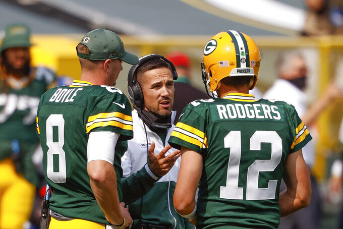 FILE - In this Sept. 20, 2020, file photo, Green Bay Packers coach Matt LaFleur speaks to quarterbacks Aaron Rodgers (12) and Tim Boyle (8) during a timeout in the team's NFL football game against the Detroit Lions in Green Bay, Wis. All the concerns about how well LaFleur would work with veteran quarterback Rodgers have disappeared near the end of their second season together. LaFleur, who came to Green Bay after one unremarkable season as the Tennessee Titans' offensive coordinator, has teamed with Rodgers to make Green Bay one of the NFL's most dynamic offenses. (AP Photo/Jeffrey Phelps, File)