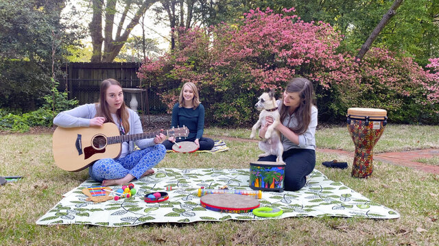 In this April 10, 2020 image from video, music therapists for St. Jude Children's Research Hospital, from left, Celeste Douglas, intern Abigail Parrish and Amy Love record a session in Love's backyard in Memphis, Tennessee. The group uploads their weekly sessions to YouTube so patients can continue receiving bedside music therapy. (Courtesy of Bryan Piras via AP)