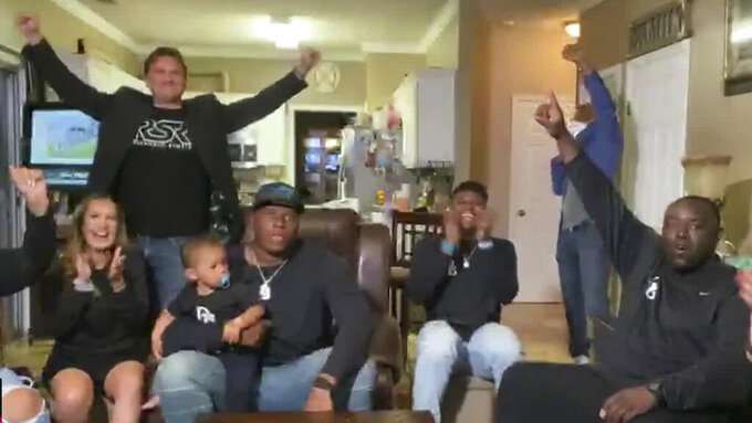In this still image from video provided by the NFL, Derrick Brown, wearing cap, watches during the NFL football draft Thursday, April 23, 2020, as people with him applaud his selection by the Carolina Panthers. (NFL via AP)