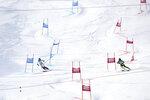 Slovakia's Petra Vlhova, left, and Sweden's Anna Swenn-larsson compete during an alpine ski, women's parallel slalom World Cup in St. Moritz, Switzerland, Sunday, Dec. 15, 2019. (AP Photo/Sergio Bisi)