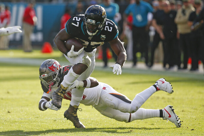Jacksonville Jaguars running back Leonard Fournette (27) tries to get around Tampa Bay Buccaneers safety Mike Edwards, during the second half of an NFL football game Sunday, Dec. 1, 2019, in Jacksonville, Fla. (AP Photo/Stephen B. Morton)