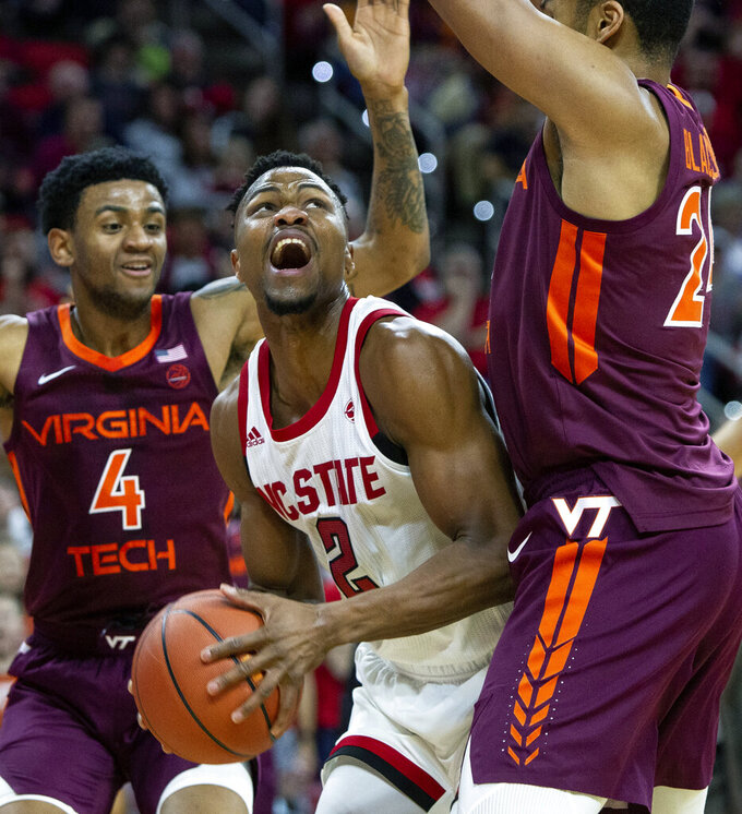 North Carolina State's Torin Dorn (2) is trapped on the baseline by Virginia Tech's Kerry Blackshear Jr., right, and Virginia Tech's Nickeil Alexander-Walker (4) during the first half of an NCAA college basketball game in Raleigh, N.C., Saturday, Feb. 2, 2019. (AP Photo/Ben McKeown)
