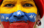 Her face painted in the colors of the national flag, a supporter of opposition leader Juan Guaido, Venezuela's self-proclaimed interim president, waits for his arrival in Los Teques, Miranda State, Venezuela, Saturday, March 30, 2019. Guaido addressed the crowd while Maduro loyalists gathered for what was billed as an