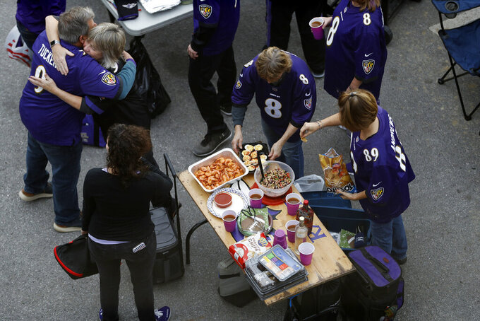 Baltimore Ravens fans tailgate ahead of the first half of an NFL divisional playoff football game between the Baltimore Ravens and the Tennessee Titans, Saturday, Jan. 11, 2020, in Baltimore. (AP Photo/Julio Cortez)