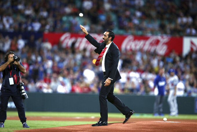 FILE - In this March 22, 2014, file photo, Australian of the year Australian Football League player Adam Goodes throws out the ceremonial first pitch before the Major League Baseball opening game Between the Los Angeles Dodgers and Arizona Diamondbacks at the Sydney Cricket ground in Sydney. Goodes has declined an offer to be inducted into the Melbourne-based AFL's Hall of Fame. (AP Photo/Rick Rycroft, File)