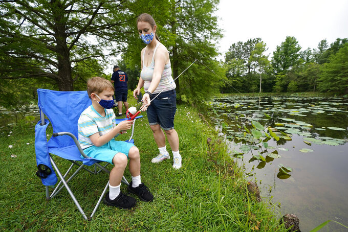 Valerie Sanchez, right, hand a fishing pole to her son, Zachary, 7, Monday, April 20, 2020, at Sheldon Lake State Park and Environmental Learning Center in Houston. Texas Gov. Greg Abbott has ordered state parks to reopen Monday after being closed due to the COVID-19 outbreak. (AP Photo/David J. Phillip)