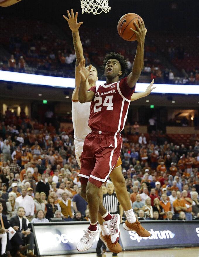 Oklahoma guard Jamal Bieniemy (24) scores past Texas forward Kamaka Hepa (33) during the first half of an NCAA college basketball game in Austin, Texas, Wednesday, Jan. 8, 2020. (AP Photo/Eric Gay)