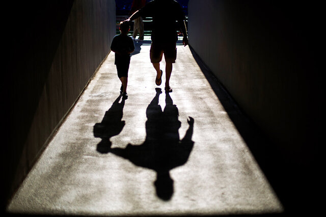 FILE - In this Saturday, April 26, 2014 file photo, a father and son cast a shadow as they walk through a tunnel before the start of a baseball game in Atlanta. A rigorous U.S. government-led study released on Tuesday, Jan. 7, 2020 found that zinc and folic acid supplements don't boost men's fertility, despite promotional claims that they do. (AP Photo/David Goldman)