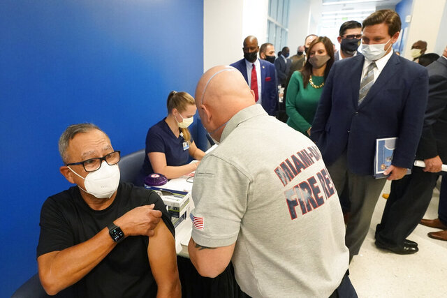 FILE - In this Jan. 4, 2021, file photo, Florida Gov. Ron DeSantis, right rear, watches as Carlos Dennis, left, 65, rolls up his sleeve so that Miami-Dade County Fire Rescue paramedic, Capt. Javier Crespo, can administer a COVID-19 vaccine shot at Jackson Memorial Hospital in Miami. Florida was one of the first states to throw open vaccine eligibility to members of the general public over 65, leading to rumors that tourists and day-trippers are swooping into the state solely for the jab.  (AP Photo/Wilfredo Lee, File)