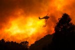 FILE - In this Aug. 12, 2020, file photo, a helicopter drops water on the Lake Hughes Fire in Angeles National Forest north of Santa Clarita, Calif. A huge forest fire that prompted evacuations north of Los Angeles flared up around noon Saturday, Aug. 15, sending up a cloud of smoke as it headed toward thick, dry brush in the Angeles National Forest. Evacuation orders remain in effect for the western Antelope Valley because erratic winds in the forecast could push the fire toward homes. Record-breaking heat is possible through the weekend, with triple-digit temperatures and unhealthy air predicted for many parts of the state. (AP Photo/Ringo H.W. Chiu, File)