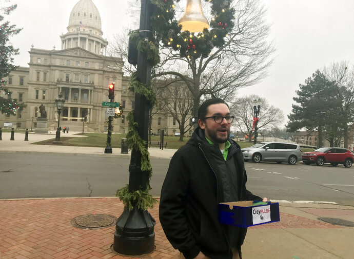 Lansing City Pulse reporter Kyle Kaminski stands outside Lansing City Hall, across the street from the Capitol and hands out free joints, Thursday, Dec. 6, 2018, in Lansing, Mich. The alternative weekly newspaper did so to mark the official legalization of recreational marijuana in Michigan. (Sarah Lehr/Lansing State Journal via AP)