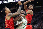 Boston Celtics guard Jaylen Brown (7) fights for rebound position against Atlanta Hawks forwards John Collins, left, and Cam Reddish during the first quarter of an NBA basketball game, Friday Jan. 3, 2020, in Boston. (AP Photo/Elise Amendola)