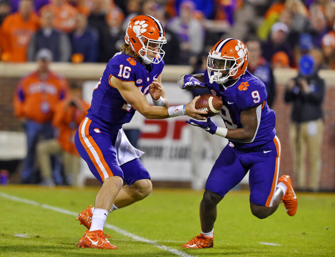 FILE - In this Nov. 17, 2018, file photo, Clemson quarterback Trevor Lawrence hands the ball off to running back Travis Etienne during the first half of an NCAA college football game against Duke in Clemson, S.C. Clemson's high-octane offense is led by the pair of young, talented offensive players. (AP Photo/Richard Shiro, File)