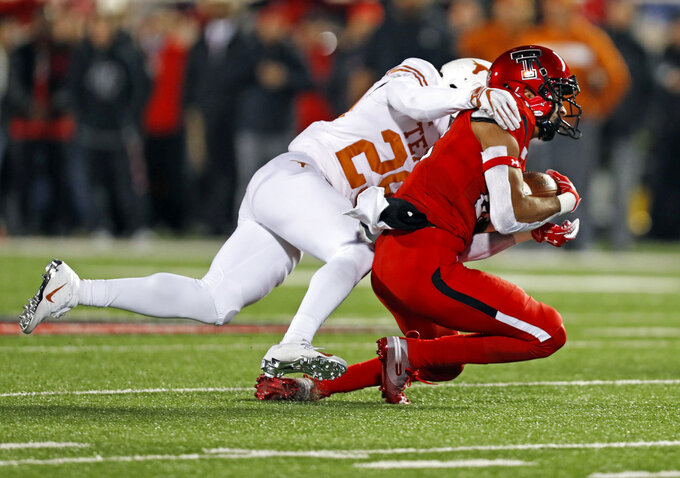 Texas Tech's Seth Collins (22) is tackled by Texas' Josh Thompson (29) during the first half of an NCAA college football game Saturday, Nov. 10, 2018, in Lubbock, Texas. (AP Photo/Brad Tollefson)