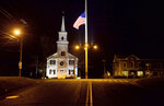 FILE - In this Dec. 15, 2012 file photo, a U.S. flag flies at half-staff on Main Street in Newtown, Conn., in honor of the 26 students and staff killed in a shooting at the Sandy Hook Elementary school. Vigils and church services were held Saturday, Dec. 14, 2019, in Newtown to mark the seventh anniversary of the Dec. 14, 2012, shooting and remember victims of other gun violence. (AP Photo/David Goldman, File)