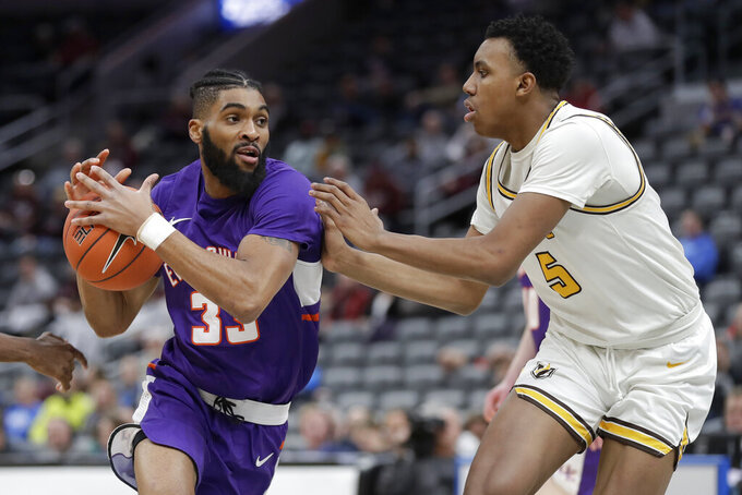 Evansville's K.J. Riley (33) heads to the basket as Valparaiso's Donovan Clay (5) defends during the first half of an NCAA college basketball game in the first round of the Missouri Valley Conference men's tournament Thursday, March 5, 2020, in St. Louis. (AP Photo/Jeff Roberson)