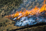 FILE - In this July 30, 2018, file photo, firefighters control the Tollgate Canyon fire as it burns near Wanship, Utah. The Trump administration is proposing an ambitious plan to slow Western wildfires by bulldozing, mowing or revegetating large swaths of land along 11,000 miles of terrain in the West. The plan announced this summer would create strips of land known as