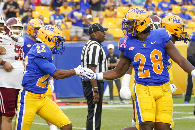 Pittsburgh running back Vincent Davis (22) is greeted by tight end Kyi Wright (28) after scoring a touchdown against Massachusetts during the second half of an NCAA college football game, Saturday, Sept. 4, 2021, in Pittsburgh. Pittsburgh won 51-7.(AP Photo/Keith Srakocic)