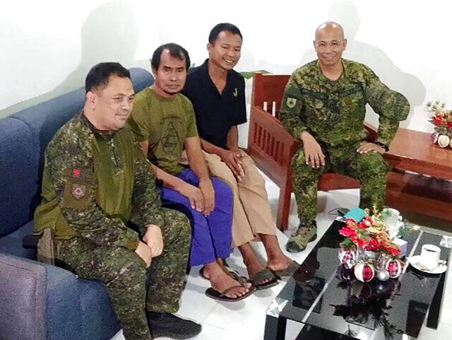 In this photo provided by the Western Mindanao Command, rescued Indonesians Maharudin Lunani, second from left, and Samion Bin Maniue, second from right, pose with Major General Corleto Vinluan, center, commander joint task force Sulu, in Jolo, Sulu, southern Philippines on Sunday Dec. 22, 2019. Philippine forces rescued two of three Indonesian hostages Sunday after a gunbattle with their captors from the Muslim militant group Abu Sayyaf in the southern jungles, a regional military commander said. (Armed Forces of the Philippines, Western Mindanao Command via AP)
