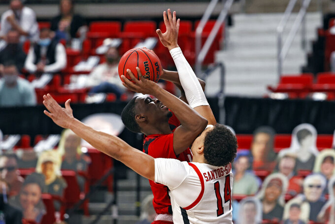 Incarnate Word's Bradley Akhile (1) shoots, and is fouled by Texas Tech's Marcus Santos-Silva (14) during the second half of an NCAA college basketball game Tuesday, Dec. 29, 2020, in Lubbock, Texas. (AP Photo/Brad Tollefson)