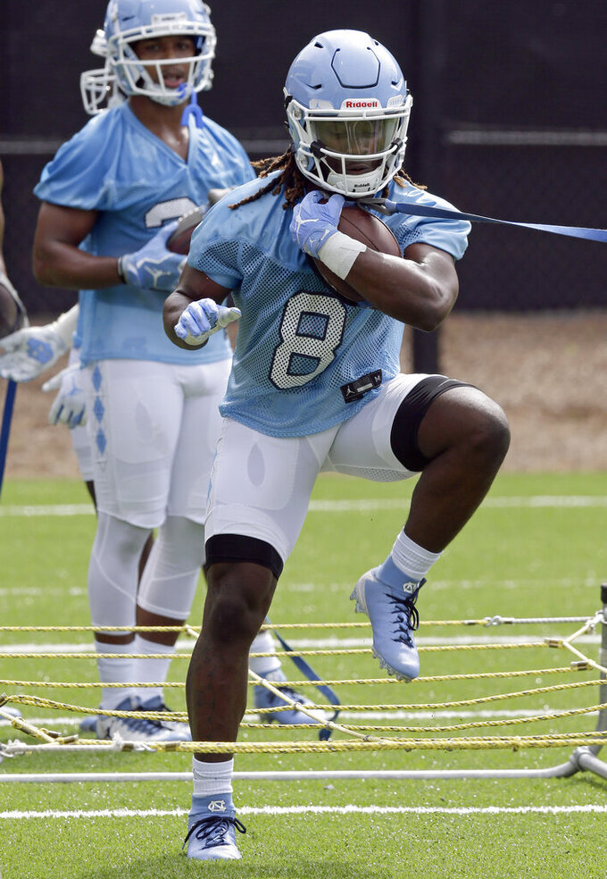North Carolina running back Michael Carter (8) runs a drill during NCAA college football practice Friday, Aug. 2, 2019 in Chapel Hill, N.C. (AP Photo/Gerry Broome)