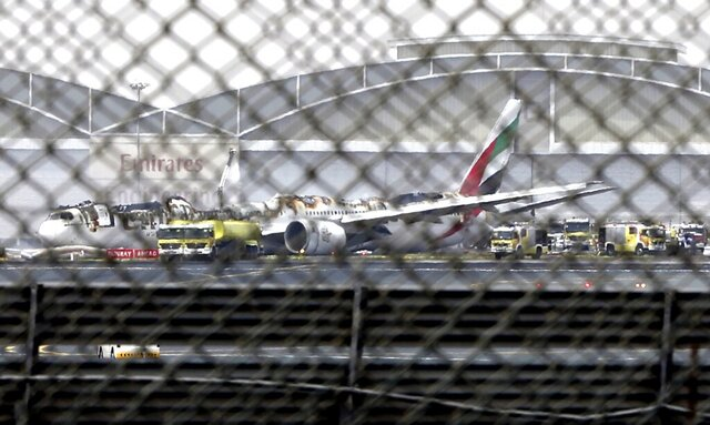 FILE - In this Aug 3, 2016 file photo, a damaged Boeing 777 is seen at the Dubai airport after it crash-landed, in Dubai, United Arab Emirates. An investigative report released Thursday, Feb. 6, 2020, found that the pilots of an Emirates flight that crashed in 2016 and caught fire in Dubai failed to realize the engines of their Boeing 777 remained idle as they tried to take off from a failed landing attempt. (AP Photo/Jon Gambrell, File)