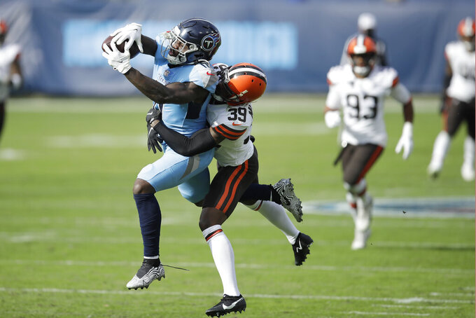 Tennessee Titans wide receiver A.J. Brown (11) makes a catch as he is defended by Cleveland Browns cornerback Terrance Mitchell (39) in the first half of an NFL football game Sunday, Dec. 6, 2020, in Nashville, Tenn. (AP Photo/Ben Margot)