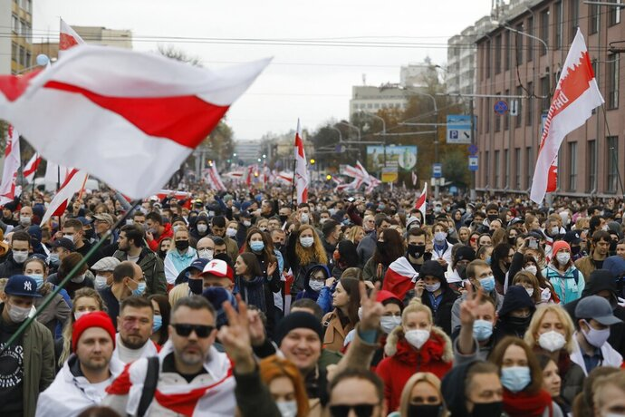 People with old Belarusian national flags march during an opposition rally to protest the official presidential election results in Minsk, Belarus, Sunday, Oct. 25, 2020. The demonstrations were triggered by official results giving President Alexander Lukashenko 80% of the vote in the Aug. 9 election that the opposition insists was rigged. Lukashenko, who has ruled Belarus with an iron fist since 1994, has accused the United States and its allies of fomenting unrest in the ex-Soviet country. (AP Photo)