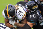 Pittsburgh Steelers running back Benny Snell Jr. (24) is stopped by Jacksonville Jaguars defensive end Adam Gotsis (96) after a short gain during the first half of an NFL football game, Sunday, Nov. 22, 2020, in Jacksonville, Fla. (AP Photo/Matt Stamey)