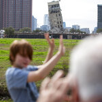 Randy Gibson takes a photo of his son Andrew, 11, in front of the 'Leaning Tower of Dallas' on Monday, Feb. 17, 2020 in Dallas. A demolition of the former Affiliated Computer Services tower on Sunday morning left the central core behind. (Juan Figueroa/The Dallas Morning News via AP)