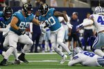 Jacksonville Jaguars running back James Robinson (30) evades tackle attempt by the Dallas Cowboys as he carries the ball for a gain in the first half of a preseason NFL football game in Arlington, Texas, Sunday, Aug. 29, 2021. (AP Photo/Michael Ainsworth)