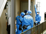 Police investigators head to the house of suspect Ayumi Kuboki in Yokohama. Japanese authorities raided Thursday, July 12, 2018, the apartment of the nurse who was arrested on suspicion of poisoning to death at least two elderly patients at a terminal care hospital.(Yuya Shino/Kyodo News via AP)