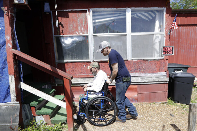 In this April 16, 2019, photo, Johnny Gibbs helps his disabled father, Mike, 65, into their home in Liberty, Tenn. Johnny Gibbs has been trying to get a valid driver's license for 20 years, but he can't afford it. To punish him for high school truancy in 1999, Tennessee suspended his ability to get a license until he turned 21. When Gibbs couldn't pay for traffic violations, he ended up serving jail time and probation. But rather than wiping his fines and allowing him to obtain a valid license, he wound up even more deeply in debt because he had to pay a monthly supervision fee to a private probation company. (AP Photo/Mark Humphrey)