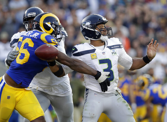File-This Nv. 11, 2018, file photo shows Los Angeles Rams defensive end Dante Fowler forcing a fumble by Seattle Seahawks quarterback Russell Wilson during the second half in an NFL football game in Los Angeles.  Fowler has re-signed with the Los Angeles Rams, passing up a shot at unrestricted free agency to stay with the NFC champions. The Rams announced a deal Sunday, March 10, 2019, to keep Fowler, but didn't disclose the terms. (AP Photo/Alex Gallardo, File)