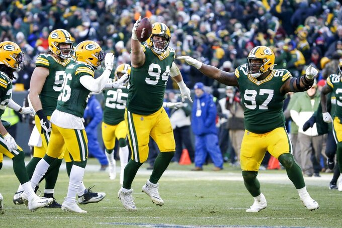 Green Bay Packers' Dean Lowry celebrates his interception during the second half of an NFL football game against the Chicago Bears Sunday, Dec. 15, 2019, in Green Bay, Wis. (AP Photo/Mike Roemer)