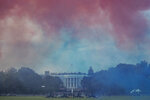 The White House in obscured by Red and Blue smoke floating on the Ellipse during a