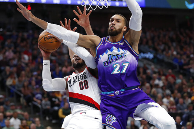 Portland Trail Blazers forward Carmelo Anthony (00) is fouled by Utah Jazz center Rudy Gobert (27) during the second quarter of an NBA basketball game, Thursday, Dec. 26, 2019, in Salt Lake City. (AP Photo/Jeff Swinger)