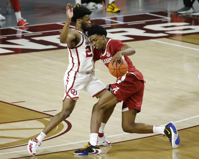 Alabama's Herbert Jones (1) goes against Oklahoma's Elijah Harkless (24) during the second half of an NCAA college basketball game in Norman, Okla., Saturday, Jan. 30, 2021. (AP Photo/Garett Fisbeck)