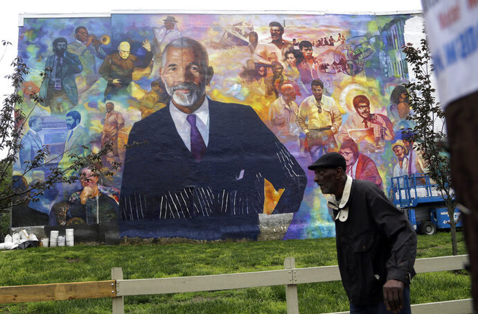 A pedestrian walks past a mural of journalist Ed Bradley, Wednesday, May 16, 2018 in Philadelphia. The mural, by artist Ernel Martinez, is in the Belmont neighborhood of west Philadelphia where Bradley grew up. A free public dedication of the mural is scheduled for Saturday May 19. (AP Photo/Jacqueline Larma)