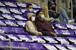 Fans sit surrounded by unsold seats as they watch TCU play Northwestern State in the second half of an NCAA college basketball game in Fort Worth, Texas, Thursday, Dec. 3, 2020. The unsold seats are covered by signs that ask fans to remain socially distant. (AP Photo/Tony Gutierrez)