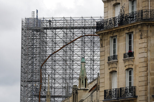 A worker stands on a scaffolding at Notre Dame cathedral, Friday, July 10, 2020 in Paris. Notre Dame Cathedral will be rebuilt just the way it stood before last year's devastating fire. (AP Photo/Thibault Camus)