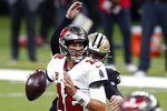 Tampa Bay Buccaneers quarterback Tom Brady (12) scrambles under pressure from New Orleans Saints defensive end Trey Hendrickson in the first half of an NFL football game in New Orleans, Sunday, Sept. 13, 2020. (AP Photo/Butch Dill)