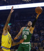 Boston Celtics' Jayson Tatum, right, lays up a shot past Golden State Warriors' Willie Cauley-Stein during the first half of an NBA basketball game Friday, Nov. 15, 2019, in San Francisco. (AP Photo/Ben Margot)