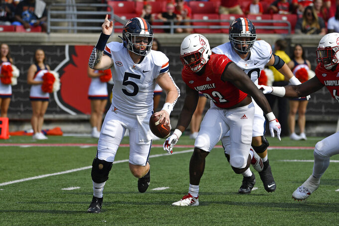Virginia quarterback Brennan Armstrong (5) is pursued by Louisville linebacker Yasir Abdullah (22) during the first half of an NCAA college football game in Louisville, Ky., Saturday, Oct. 9, 2021. (AP Photo/Timothy D. Easley)