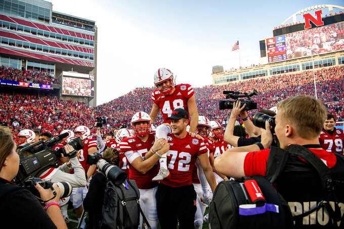 FILE - In this Saturday, Oct. 5, 2019, file photo, Nebraska kicker Lane McCallum (48) is carried off the field by his teammates after kicking the game-winning field goal as time expired in an NCAA college football game against Northwestern, in Lincoln, Neb. Nebraska's 24-sport program has about 600 athletes and is one of a handful that makes money. Though a 10% budget cut was announced recently, the program is able to absorb the cost of coronavirus testing, in part because of its affiliation with the university's medical school. (Francis Gardler/Lincoln Journal Star via AP, File)