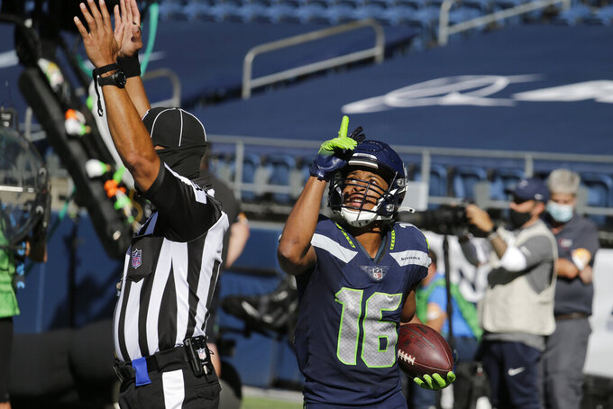 Seattle Seahawks wide receiver Tyler Lockett holds the ball and reacts after scoring a touchdown against the Dallas Cowboys during the first half of an NFL football game, Sunday, Sept. 27, 2020, in Seattle. (AP Photo/John Froschauer)