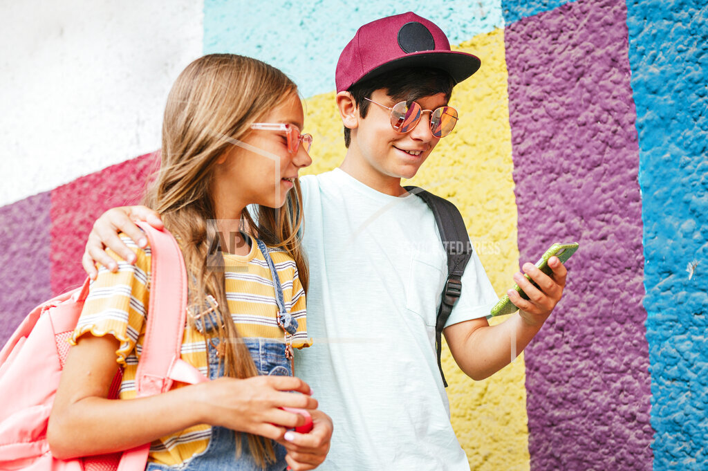 Smiling boy using mobile phone while walking with arm around female friend by wall