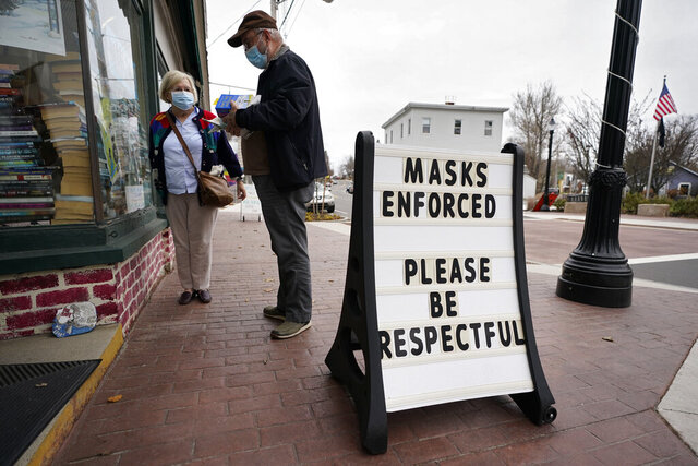 Shoppers comply with the mask regulations to help prevent the spread of the coronavirus at Bridgton Books, Friday, Nov. 13, 2020, in Bridgton, Maine. With the coronavirus coming back with a vengeance across the country and the U.S. facing a long, dark winter, governors and other elected officials are showing little appetite for reimposing the kind of lockdowns and large-scale business closings seen last spring. (AP Photo/Robert F. Bukaty)