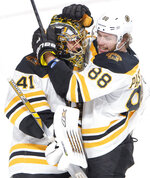 Boston Bruins right wing David Pastrnak (88) hugs Boston Bruins goaltender Jaroslav Halak (41) after shutting out the Montreal Canadiens 4-0 in NHL hockey action in Montreal on Monday, Dec. 17, 2018. (Ryan Remiorz/The Canadian Press via AP)