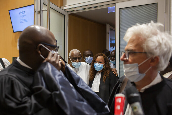 Former track federation president Lamine Diack, centre left, leaves the courtroom after his trial in Paris, France, Wednesday, September 16, 2020. Diack has been sentenced to two years in prison for his role in a scheme that allowed Russian athletes who paid hush money to keep competing when they should have been suspended for doping.(AP Photo/Rafael Yaghobzadeh)